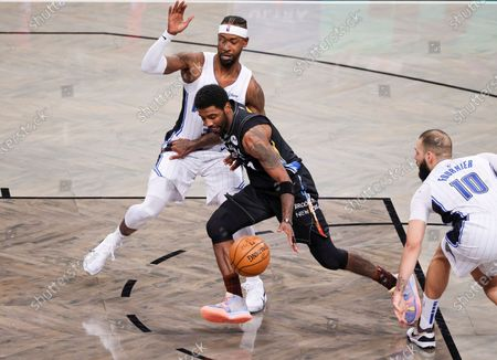 Stock Picture of The Nets' Kyrie Irving (C) drives past Magic players Terrence Ross (L) and Evan Fournier (R) during the second half of the NBA basketball game between the Orlando Magic and the Brooklyn Nets at the Barclays Center in the Brooklyn borough of New York, USA, 25 February 2021.