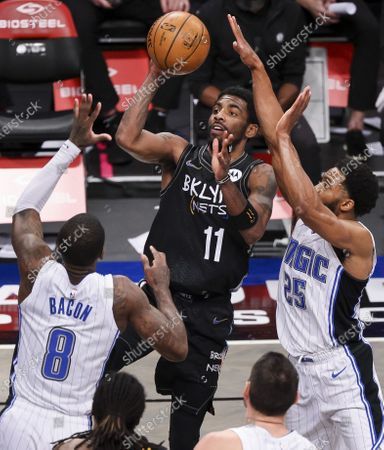 The Nets' Kyrie Irving (C) drives to the basket as Magic players Dwayne Bacon (L) and Chasson Randle (R) defend during the second half of the NBA basketball game between the Orlando Magic and the Brooklyn Nets at the Barclays Center in the Brooklyn borough of New York, USA, 25 February 2021.