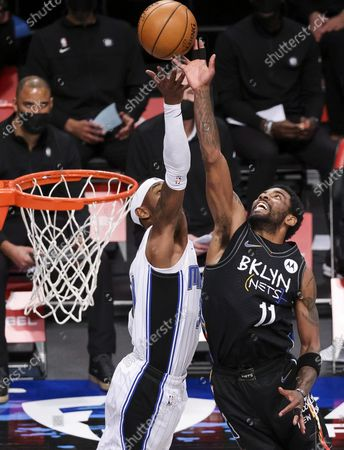 The Nets' Kyrie Irving (R) and the Magic's Terrence Ross (L) battle for a rebound during the second half of the NBA basketball game between the Orlando Magic and the Brooklyn Nets at the Barclays Center in the Brooklyn borough of New York, USA, 25 February 2021.