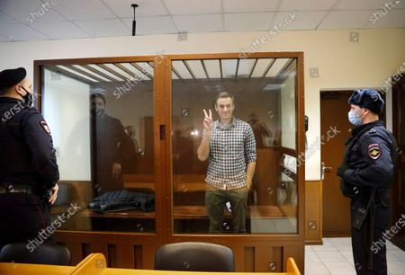 Opposition leader Alexei Navalny stands in a cage in the Babuskinsky District Court in Moscow, Russia, . Two trials against Navalny are being held Moscow City Court one considering an appeal against his imprisonment in the embezzlement case and another announcing a verdict in the defamation case