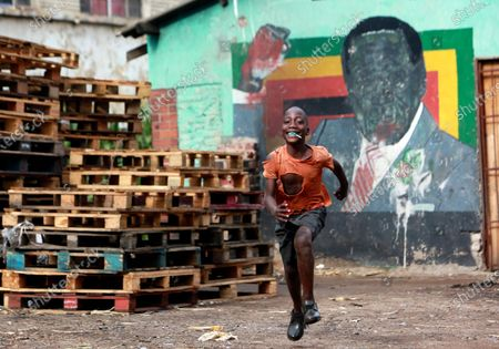 Stock Photo of Boy runs past a mural of former President Robert Mugabe in Harare, . The Zimbabwean leader died in 2019