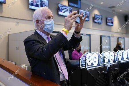 Sen. John Cornyn, R-Texas, uses his phone as President Joe Biden tours the Harris County Emergency Operations Center with Texas Gov. Greg Abbott, in Houston