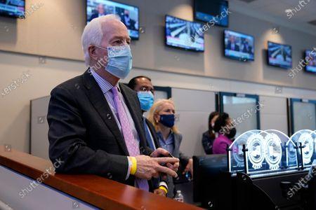Sen. John Cornyn, R-Texas, listens as President Joe Biden tours the Harris County Emergency Operations Center with Texas Gov. Greg Abbott, in Houston