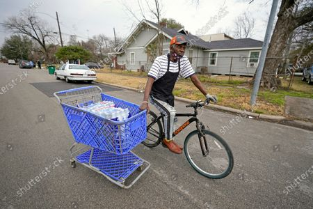 Stock Picture of Fifth Ward resident Mark Johnson pulls a shopping cart with donated water back to his apartment, which still does not have running water, in Houston. President Joe Biden and his wife Jill are visiting Houston Friday to survey damage caused by severe winter weather and encourage people to get their coronavirus shots. At least 40 people died in Texas as a result of the storm and more than 1 million residents are still under a boil water notice