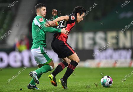 Milot Rashica (L) of Bremen in action against Makoto Hasebe (R) of Frankfurt during the German Bundesliga soccer match between Werder Bremen and Eintracht Frankfurt in Bremen, Germany, 26 February 2021.