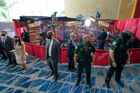 Officials and Orange County Sherrif Deputies block off a section keep spectators away as Donald Trump Jr., back center, takes part in an interview at the Conservative Political Action Conference (CPAC), in Orlando, Fla