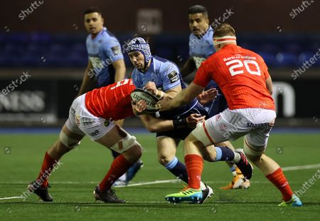 Matthew Morgan of Cardiff Blues is tackled by Nick McCarthy and Gavin Coombes of Munster.