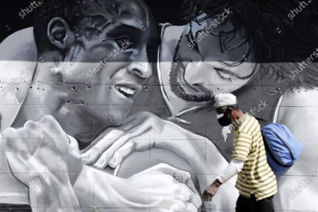 A pedestrian walks past a mural showing NBA players Pau Gasol (R) and Kobe Bryant (L) depicting the friendship between the two Los Angeles Lakers players in Los Angeles, California, USA, 26 February 2021. A year after the passing of basketball player Kobe Bryant and his daughter Gianna, Los Angeles still mourns the loss of a legend through murals all over the city and county. Kobe Bryant died in a helicopter crash on 26 January 2020.