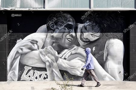 Stock Picture of A pedestrian walks past a mural showing NBA players Pau Gasol (R) and Kobe Bryant (L) depicting the friendship between the two Los Angeles Lakers players in Los Angeles, California, USA, 26 February 2021. A year after the passing of basketball player Kobe Bryant and his daughter Gianna, Los Angeles still mourns the loss of a legend through murals all over the city and county. Kobe Bryant died in a helicopter crash on 26 January 2020.