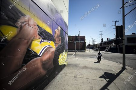 A pedestrian stands next to a mural of NBA player Kobe Bryant in a long strip of murals by various street artists and focused on basketball stars in Los Angeles, California, USA, 26 February 2021. A year after the passing of basketball player Kobe Bryant and his daughter Gianna, Los Angeles still mourns the loss of a legend through murals all over the city and county. Kobe Bryant died in a helicopter crash on 26 January 2020.