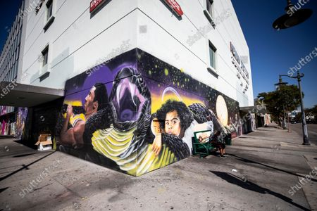 Stock Photo of A sits on a bench next to a mural of NBA player Kobe Bryant and his daughter Gianna, located close to another mural showing NBA players Pau Gasol and Kobe Bryant and depicting the friendship between the two Los Angeles Lakers players in a long strip of murals by various street artists and focusing on basketball stars in Los Angeles, California, USA, 26 February 2021. A year after the passing of basketball player Kobe Bryant and his daughter Gianna, Los Angeles still mourns the loss of a legend through murals all over the city and county. Kobe Bryant died in a helicopter crash on 26 January 2020.
