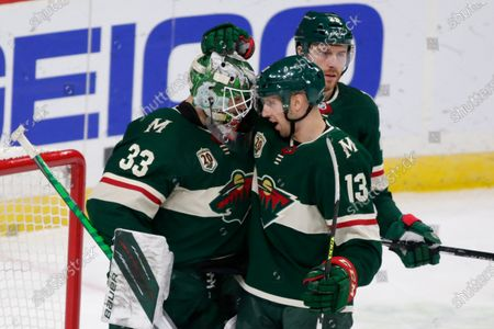 Minnesota Wild goalie Cam Talbot (33) is congratulated by center Nick Bonino (13) after defeating the Los Angeles Kings in an NHL hockey game, in St. Paul, Minn
