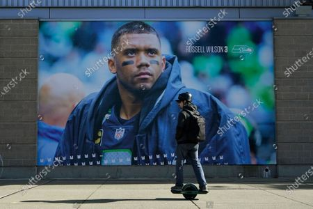 Person rides a Onewheel past a giant photo of Seattle Seahawks quarterback Russell Wilson, at Lumen Field in Seattle, where the NFL football team plays all of their home games