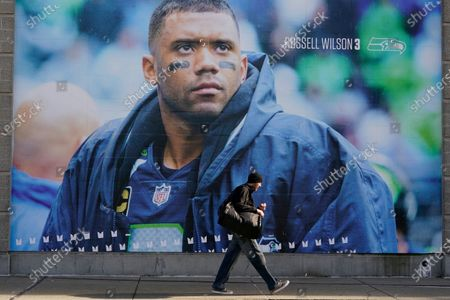 Person walks past a giant photo of Seattle Seahawks quarterback Russell Wilson, at Lumen Field in Seattle, where the NFL football team plays all of their home games