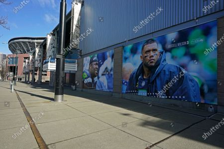 The sun shines on a giant photo of Seattle Seahawks quarterback Russell Wilson, at Lumen Field (at left) in Seattle, where the NFL football team plays all of their home games