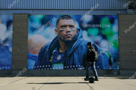 Stock Image of Person rides a Onewheel past a giant photo of Seattle Seahawks quarterback Russell Wilson, at Lumen Field in Seattle, where the NFL football team plays all of their home games