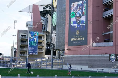 Two people walk dogs near a banner commemorating Seattle Seahawks quarterback Russell Wilson being named NFL football's Man of the Year, at Lumen Field in Seattle, where the NFL football team plays all of their home games