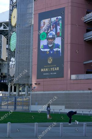 Stock Photo of Two people walk dogs near a banner commemorating Seattle Seahawks quarterback Russell Wilson being named NFL football's Man of the Year, at Lumen Field in Seattle, where the NFL football team plays all of their home games