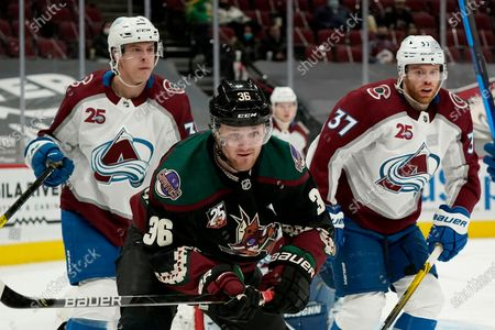 Arizona Coyotes right wing Christian Fischer (36) skates to the puck in front of Colorado Avalanche defenseman Jacob MacDonald, left, and Avalanche left wing J.T. Compher (37) during the third period of an NHL hockey game, in Glendale, Ariz. The Avalanche defeated the Coyotes 3-2