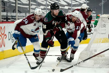 Arizona Coyotes right wing Christian Fischer (36) has the puck poked away by Colorado Avalanche left wing J.T. Compher (37) as Avalanche defenseman Jacob MacDonald (34) applies pressure during the third period of an NHL hockey game, in Glendale, Ariz. The Avalanche defeated the Coyotes 3-2