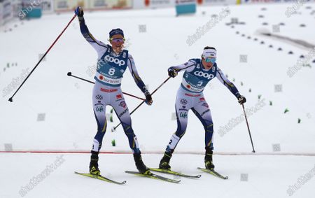 Sweden's Frida Karlsson, left, crosses the finish to take second place in the WSC Women's Skiathlon 15km cross country event at the FIS Nordic World Ski Championships in Oberstdorf, Germany