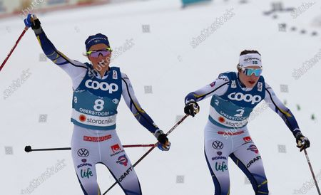 Sweden's Frida Karlsson, left, crosses the finish line to take second place in the WSC Women's Skiathlon 15km cross country event at the FIS Nordic World Ski Championships in Oberstdorf, Germany