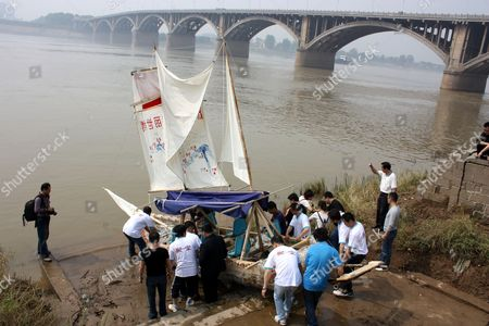 Xia Yu and his volunteer crew carry the plastic bottle boat down to the river. China.