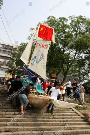Xia Yu and his volunteer crew transport the plastic bottle boat down to the river. China.
