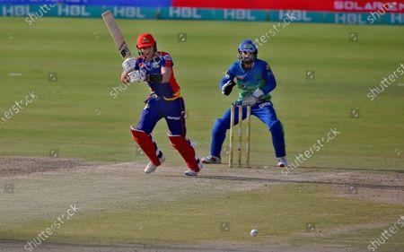 Karachi Kings' Joe Clarke, center, plays a shot while Multan Sultans' Mohammad Rizwan watches during a Pakistan Super League T20 cricket match between Karachi Kings and Multan Sultans at the National Stadium, in Karachi, Pakistan