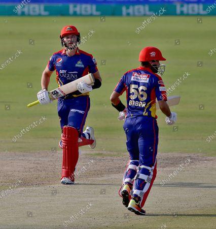 Karachi Kings' Joe Clarke, left, and Babar Azam run between the wickets during a Pakistan Super League T20 cricket match between Karachi Kings and Multan Sultans at the National Stadium, in Karachi, Pakistan