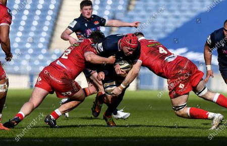 Edinburgh vs Scarlets. Edinburgh's Grant Gilchrist is tackled by Marc Jones and Morgan Jones of Scarlets