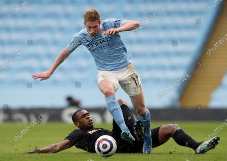 Manchester City's Kevin De Bruyne, front, duels for the ball with West Ham's Issa Diop during the English Premier League soccer match between Manchester City and West Ham United at the Etihad stadium in Manchester, England