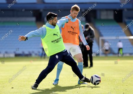 Manchester City's Sergio Aguero, front, duels for the ball with Manchester City's Kevin De Bruyne during warm up before the English Premier League soccer match between Manchester City and West Ham United at the Etihad stadium in Manchester, England