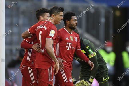 Bayern's Lucas Hernandez, left, Robert Lewandowski, center, and Serge Gnabry celebrate after a goal during a German Bundesliga soccer match between Bayern Munich and 1.FC Cologne in Munich, Germany