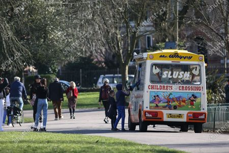 People stop for ice-cream on a beautiful Saturday in Alexandra Park.