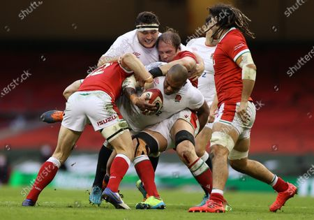 Kyle Sinckler of England is tackled by Jonathan Davies and Alun Wyn Jones of Wales.