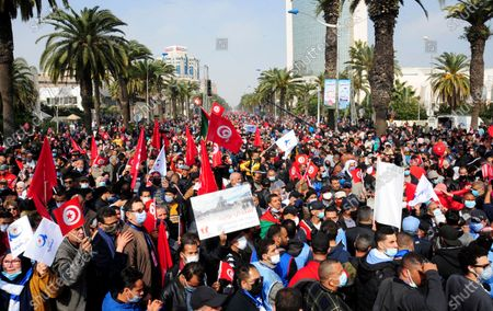 Supporters of the islamist Ennada party march with Tunisian flags during a rally in Tunis, Tunisia, . The party, Ennahdha, led by House Speaker Rached Ghannouchi, has backed Prime Minister Hichem Mechichi in his standoff with President Kais Saied over a cabinet reshuffle