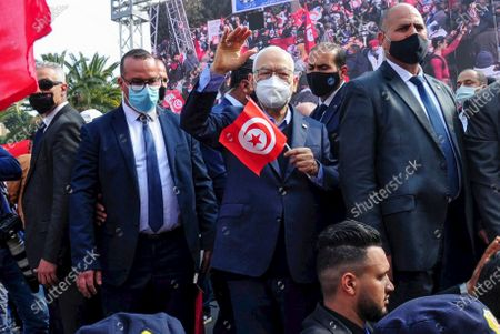 Leader of Tunisia's Islamist Ennahda party House Speaker Rached Ghannouchi waves as he holds a Tunisian flag during a rally in Tunis, Tunisia, . The party, Ennahdha, led by House Speaker Rached Ghannouchi, has backed Prime Minister Hichem Mechichi in his standoff with President Kais Saied over a cabinet reshuffle