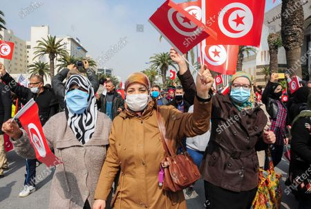 Stock Photo of Supporters of the islamist Ennada party march with Tunisian flags during a rally in Tunis, Tunisia, . The party, Ennahdha, led by House Speaker Rached Ghannouchi, has backed Prime Minister Hichem Mechichi in his standoff with President Kais Saied over a cabinet reshuffle