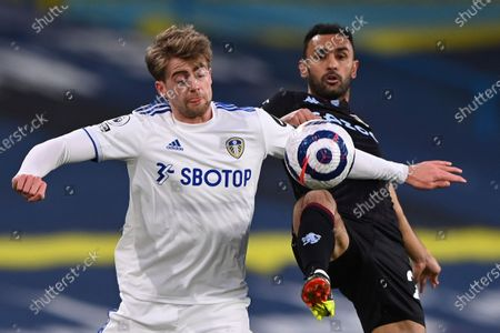 Leeds United's Patrick Bamford, left, challenges for the ball with Aston Villa's Ahmed Elmohamady during an English Premier League soccer match between Leeds United and Aston Villa at the Elland Road Stadium in Leeds, England
