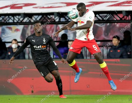 Moenchengladbach's Breel Embolo, left, looks on as Leipzig's Dayot Upamecano, right, goes for a header during the German Bundesliga soccer match between RB Leipzig and Borussia Moenchengladbach in Leipzig, Germany