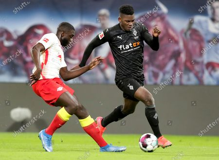 Leipzig's Dayot Upamecano, left, and Moenchengladbach's Breel Embolo, right, challenge for the ball during the German Bundesliga soccer match between RB Leipzig and Borussia Moenchengladbach in Leipzig, Germany