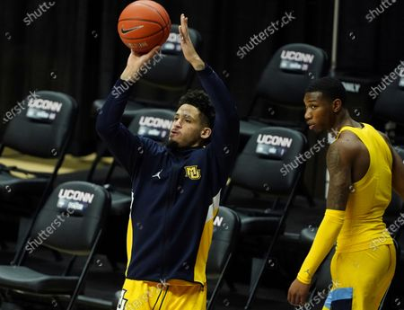 Marquette guard Jose Perez, left, and forward Jamal Cain (23) warm-up before an NCAA college basketball game, in Storrs, Conn