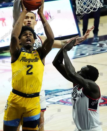 Marquette forward Justin Lewis (2) shoots the ball against Connecticut Huskies guard Tyrese Martin (behind Lewis) and forward Akok Akok (11) in the second half of an NCAA college basketball game, in Storrs, Conn