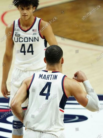 Connecticut guard Tyrese Martin (4) reacts after making a basket against the Marquette in the first half of an NCAA college basketball game, in Storrs, Conn
