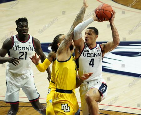 Connecticut guard Tyrese Martin, right, drives the ball against Marquette forward Theo John, center, in the first half of an NCAA college basketball game, in Storrs, Conn