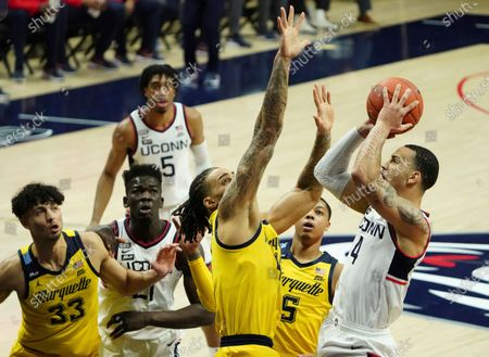 Connecticut guard Tyrese Martin, right, shoots the ball against Marquette forward Theo John, left, in the first half of an NCAA college basketball game, in Storrs, Conn