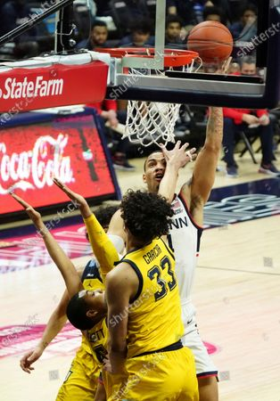 Connecticut guard Tyrese Martin (4) shoots against Marquette guard Greg Elliott (5) and forward Dawson Garcia (33) in the first half of an NCAA college basketball game, in Storrs, Conn