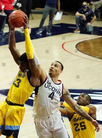 Marquette forward Jamal Cain (23) grabs a rebound against Connecticut guard Tyrese Martin (4) in the first half of an NCAA college basketball game, in Storrs, Conn