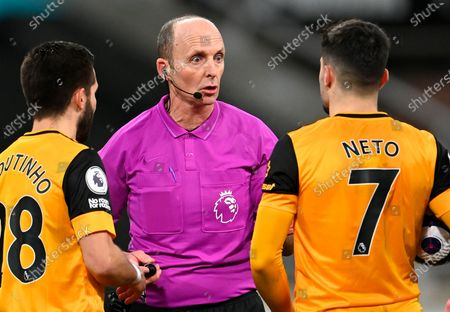 Referee Mike Dean (C) talks to Wolverhampton's Joao Moutinho (L) and Pedro Neto (R) during the English Premier League soccer match between Newcastle United and Wolverhampton Wanderers in Newcastle, Britain, 27 February 2021.